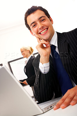 Buy stock photo Business man working by desk - Portrait of a handsome young man in a business suit working in his office. Picture taken from below.
