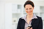 Happy business woman using a mobile phone at work
