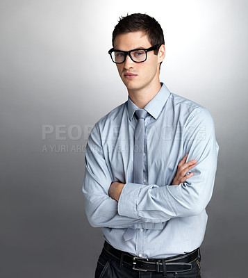 Buy stock photo Portrait of a handsome young businessman standing with folded hand against grey background