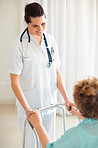Nurse helping a patient to stand on a walker