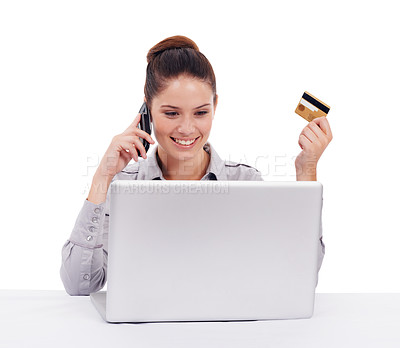 Buy stock photo Shot of a young woman seated at a laptop and holding a credit card and cellphone