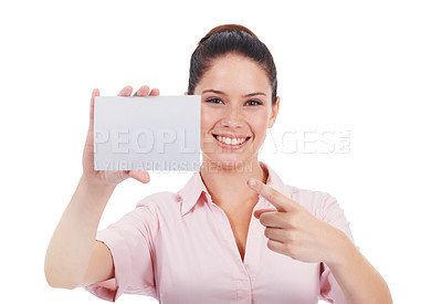 Buy stock photo Studio portrait of an surprised-looking young woman pointing at a small blank sign while isolated on white