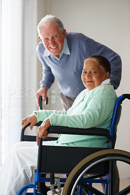 Elderly woman on a wheel chair , husband at the back