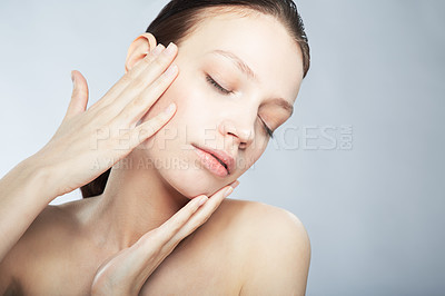 Buy stock photo Head and shoulder shot of a beautiful young woman in the nude with eyes closed and hand on her face