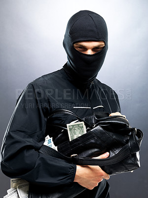 Buy stock photo Portrait of a young male burglar holding a bag full of money