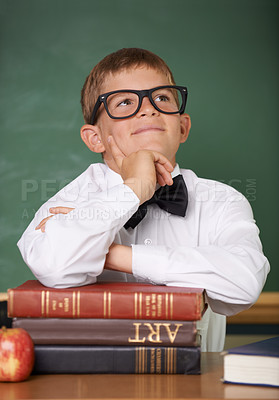 Buy stock photo A happy young schoolboy sitting behind a pile of books looking up thoughtfully