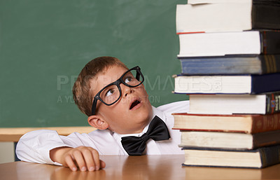 Buy stock photo A young boy wearing glasses and a bow-tie looking wearily at a large pile of books
