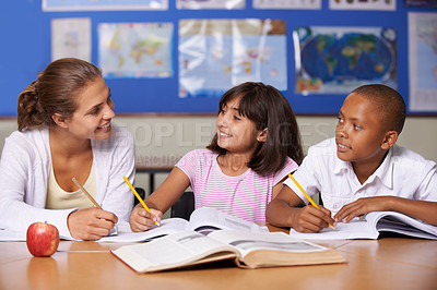 Buy stock photo A young teacher having a discussion with her two ethnic pupils while they page through a textbook