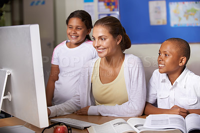 Buy stock photo young teacher teaching two ethnic children how to use a computer