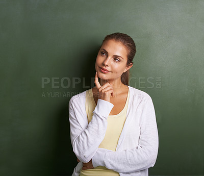 Buy stock photo A lovely young teacher standing in front of a blackboard looking thoughtful
