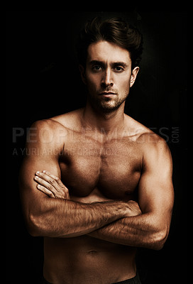 Buy stock photo Portrait of a well-built young man isolated on black with his arms crossed