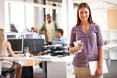 Buy stock photo Shot of a young designer holding her notepad and digital tablet with her colleagues in the background