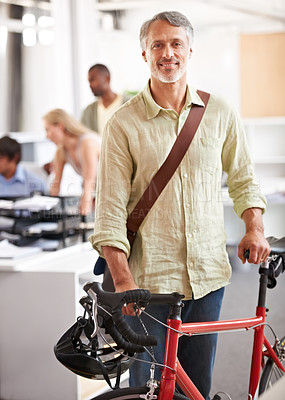Buy stock photo An environmentally conscious business leader arriving at work with his bike