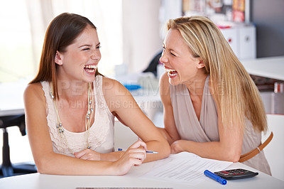 Buy stock photo Shot of two female coworkers sharing a laugh at a desk in an office