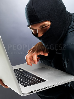 Buy stock photo Portrait of a male hacker stealing information from laptop