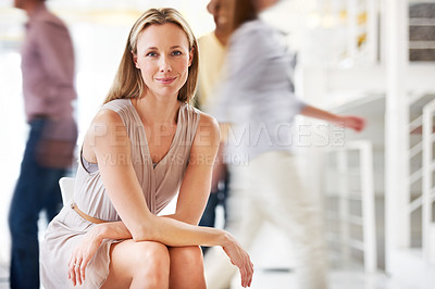 Buy stock photo A pretty mature businesswoman sitting calmly as his colleagues stream by in haste - conceptual