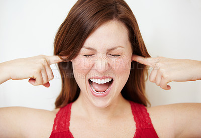 Buy stock photo An attractive young woman blocking her ears and schouting
