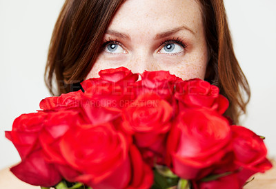 Buy stock photo An attractive young woman peering over a bouquet of roses