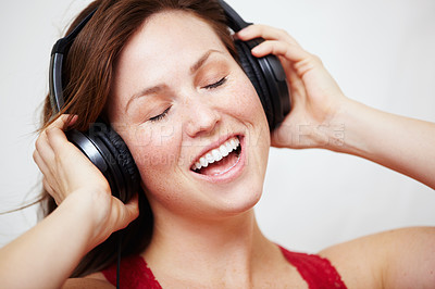 Buy stock photo An attractive young woman listening to music on her headphones