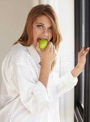 Buy stock photo An attractive young woman biting into a delicious apple