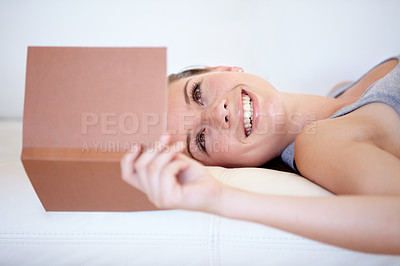 Buy stock photo A young woman reading a book while lying on the couch
