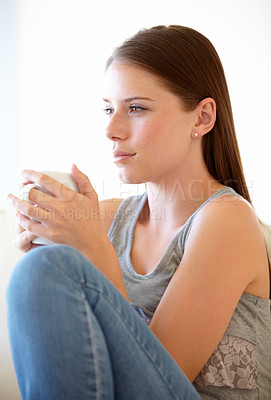 Buy stock photo A gorgeous young woman sitting on the couch with a cup of coffee