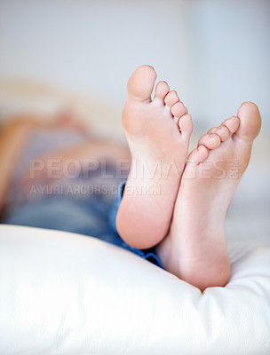 Buy stock photo Closeup of a young woman's feet as she's lying on her bed