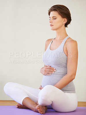 Buy stock photo A young pregnant woman sitting on an exercising mat with her legs crossed