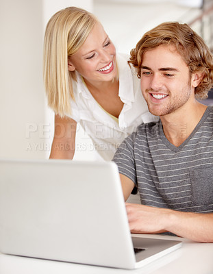 Buy stock photo A happy young couple using a laptop indoors