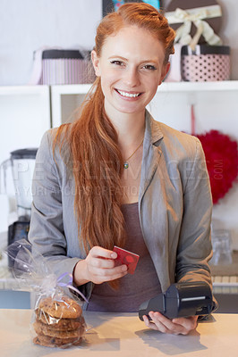 Buy stock photo Portrait of an attractive young woman swiping your card in her bakery