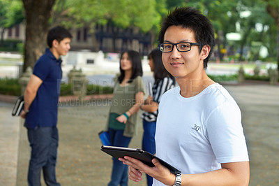 Buy stock photo Portrait of a handsome young student working on his digital tablet outside