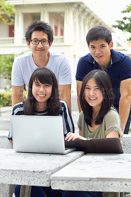 Buy stock photo Four young students sharing a laptop
