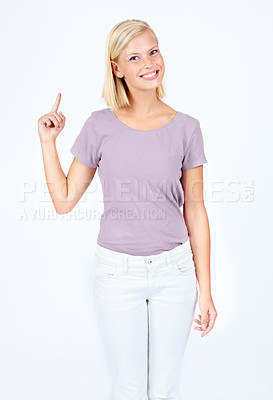 Buy stock photo Happy young woman pointing upwards while isolated on white