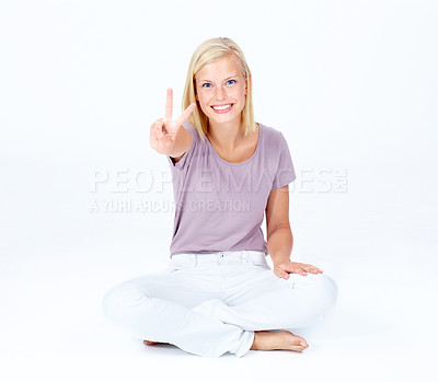 Buy stock photo Cute young woman holding out the peace sign while isolated on white