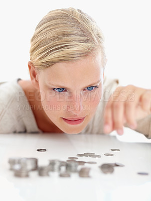 Buy stock photo Shot of a beautiful woman looking at coins on the table in front of her