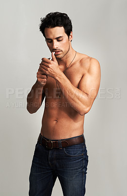 Buy stock photo A shirtless young man lighting his cigarette