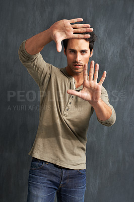 Buy stock photo Portrait of a handsome young man framing you with his hands