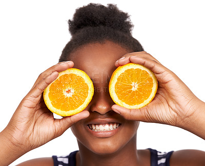 Buy stock photo Studio portrait of a happy young african american girl holding orange halves in front of her eyes isolated on white
