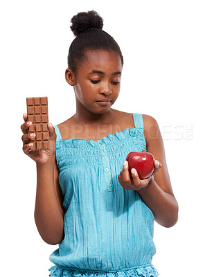 Buy stock photo Shot of a young african american girl trying to decide between eating an apple or an a piece of chocolate