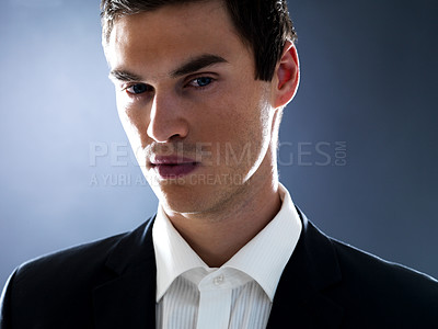 Buy stock photo Portrait of a handsome young businessman looking at you against grey background