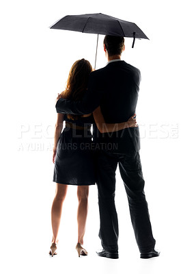 Buy stock photo Rear view of a young couple standing under umbrella over bright background
