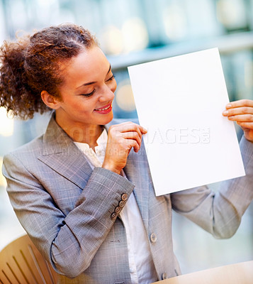 Buy stock photo Happy young African American business woman displaying a blank sheet of paper while at work