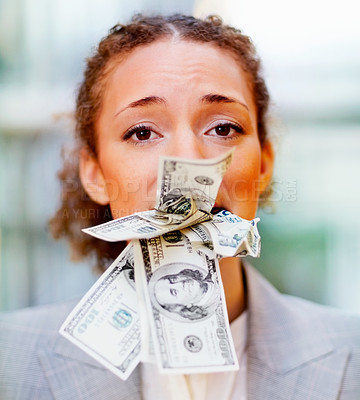 Buy stock photo Young African American business woman with her mouth stuffed with money