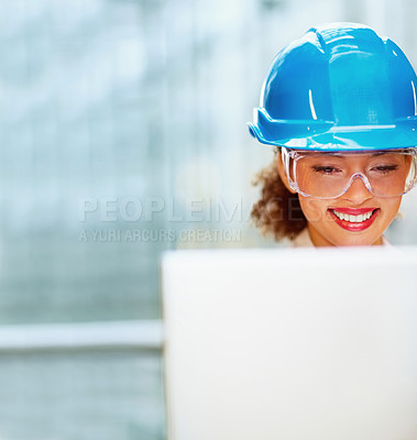 Buy stock photo Happy cute business woman wearing a hardhat while working on a laptop