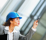 Female architect wearing a hardhat pointing upwards with a pen