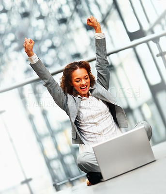 Buy stock photo Excited young business woman with her hands raised sitting on the floor working on the laptop