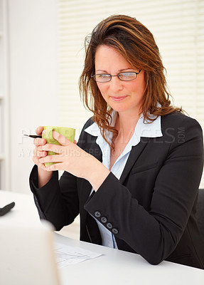 Buy stock photo Middle aged business woman having a cup of coffee at work