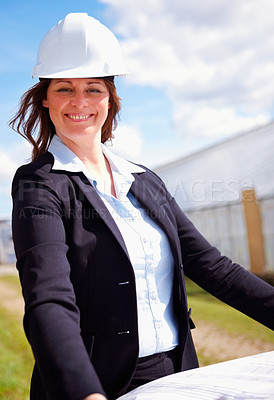 Buy stock photo Happy mature female architect with her blue prints at the construction site