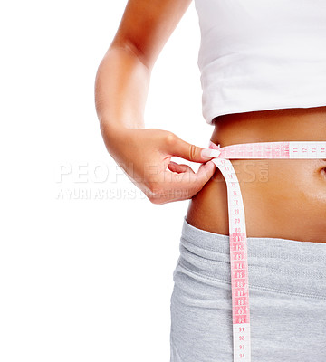 Buy stock photo Mid section of a young woman holding a measure tape around her toned abdomen