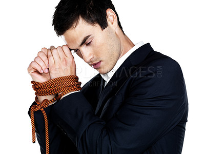Buy stock photo Upset young business man with his hands tied with a rope against white background